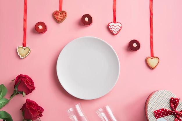Assiette rose en rose avec quatre biscuits, deux roses, une boîte cadeau en forme de coeur et deux verres