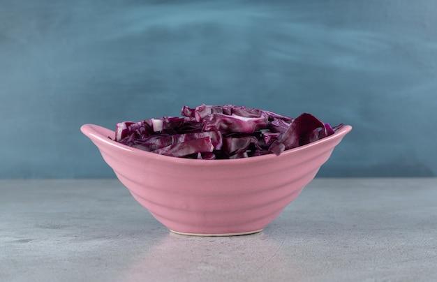 Une assiette rose avec des tranches de légumes de chou violet. photo de haute qualité