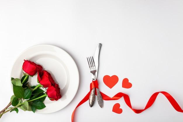 Assiette avec des roses et des couverts attachés avec un ruban rouge