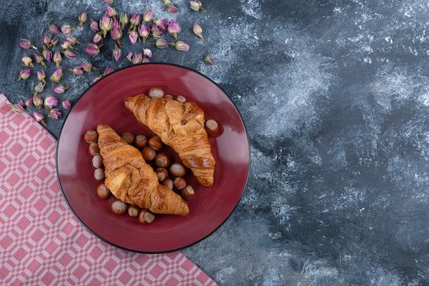 Assiette rouge de croissants sucrés aux noisettes décortiquées sur marbre.