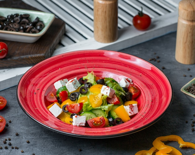 Une assiette rouge pleine de salade au fromage
