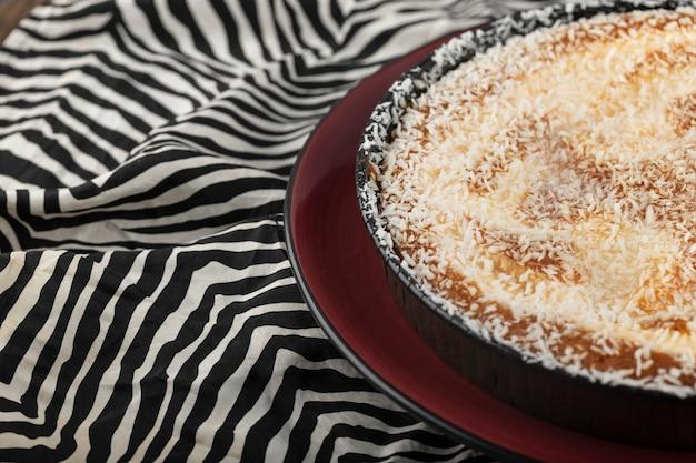 Assiette rouge de tarte sucrée avec des pépites de noix de coco sur nappe à rayures