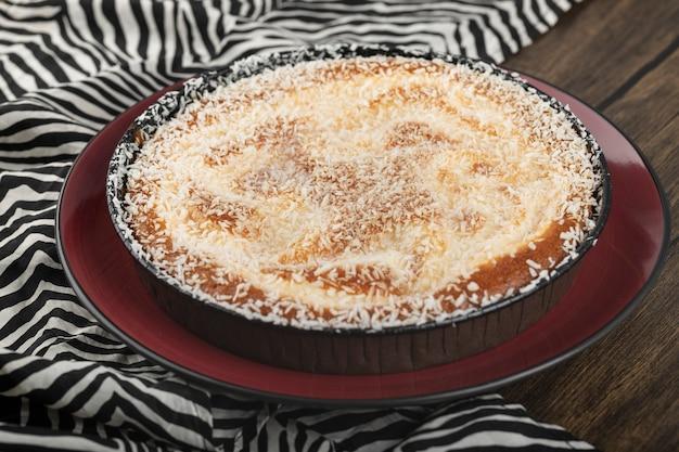 Assiette rouge de tarte sucrée avec des pépites de noix de coco sur une surface en bois