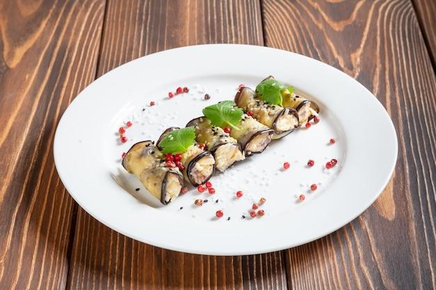Assiette avec des rouleaux d'aubergine avec du fromage et du jambon
