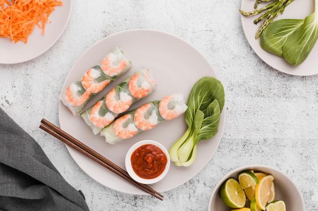 Assiette de rouleaux de crevettes avec des baguettes et du citron vert