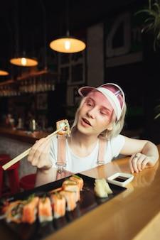 Assiette de rouleaux de sushi au restaurant avec femme tenant des baguettes