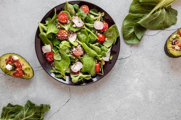 Assiette avec salade et avocat sur table