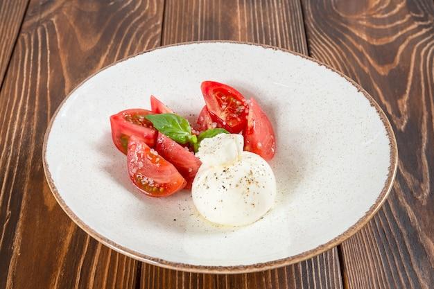 Assiette de salade caprese avec tomates resh et un morceau de mozzarella