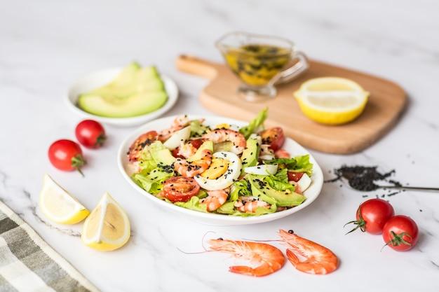 Assiette de salade fraîche aux crevettes, tomates, œufs, avocat et mélange de verdures sur blanc