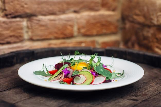 Assiette à la salade fraîche sur le baril en bois