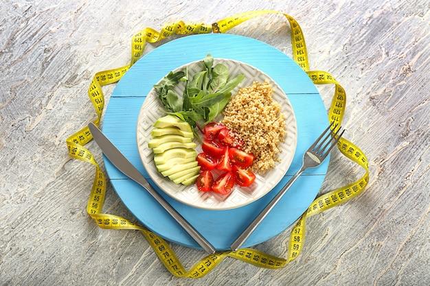 Assiette avec salade fraîche saine et ruban à mesurer sur planche de bois. notion de régime