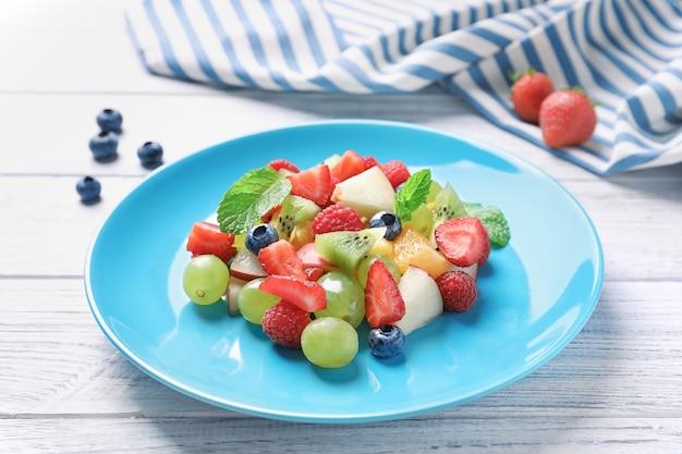 Assiette avec salade de fruits sur table en bois