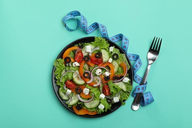 Assiette de salade grecque, ruban à mesurer et fourchette sur la surface de la menthe