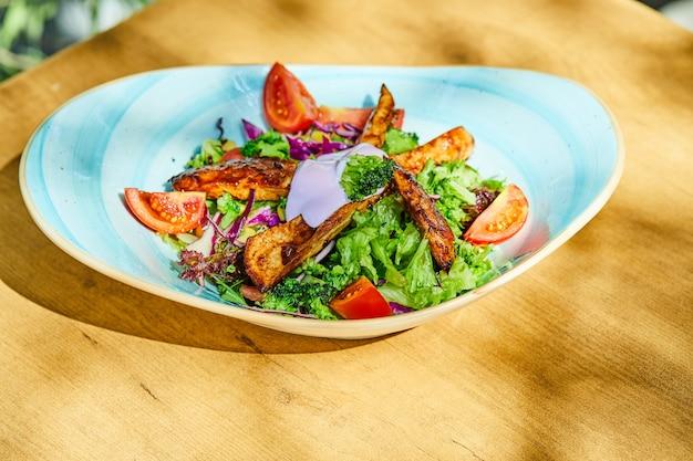 Une assiette de salade de légumes et de poulet sur table en bois
