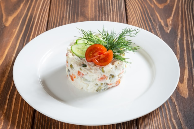 Assiette de salade russe traditionnelle olivier sur table en bois