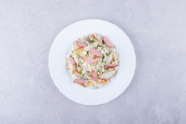 Assiette de salade avec des saucisses sur fond de pierre.