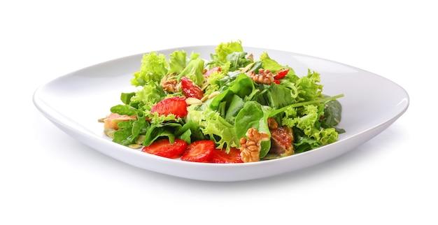 Assiette avec salade savoureuse fraîche sur une surface blanche