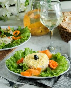 Une assiette de salas de mimosa garnie de tranches de carotte et de laitue
