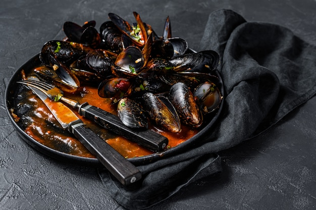 Assiette sale avec les restes du dîner, coquilles de moules. fond noir. vue de dessus