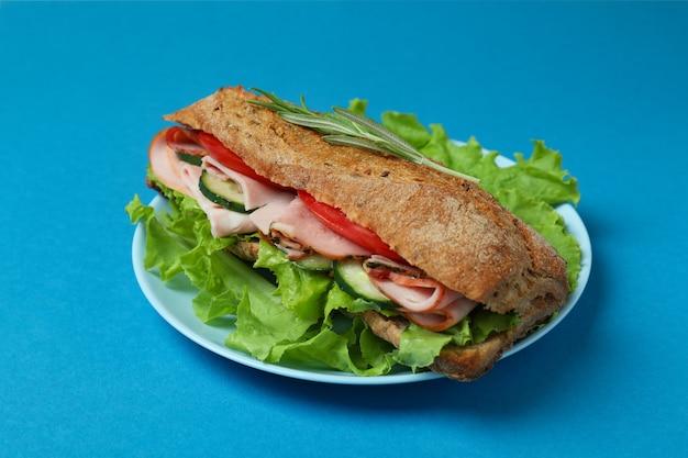 Assiette avec sandwich ciabatta sur fond bleu
