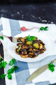 Assiette avec sauce aux champignons et concombre mariné et vert
