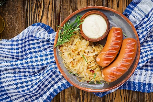 Assiette de saucisses et choucroute sur table en bois. menu traditionnel de l'oktoberfest. mise à plat. vue de dessus.