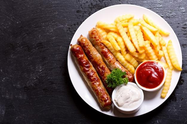 Assiette de saucisses grillées avec frites, vue du dessus