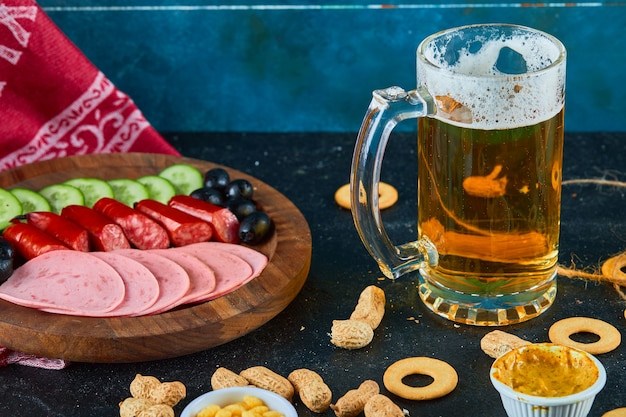 Une assiette de saucisses et un verre de bière sur une table sombre.