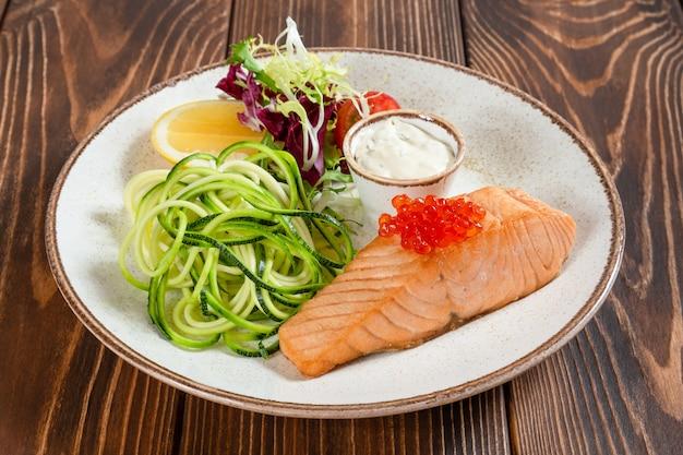 Assiette de saumon cuit à la vapeur avec du caviar rouge et des légumes sur une table en bois