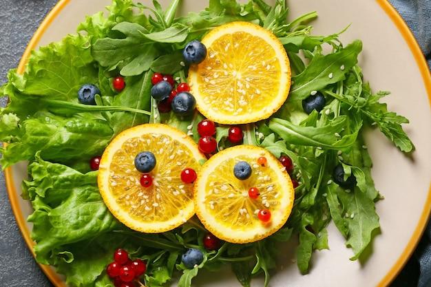 Assiette avec une savoureuse salade de roquette sur table sombre, gros plan