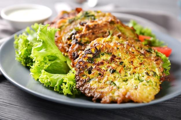 Assiette avec de savoureuses crêpes aux courgettes sur table en bois, gros plan