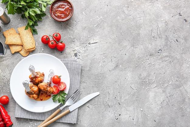 Assiette avec de savoureuses sucettes au poulet et tomates sur surface grise