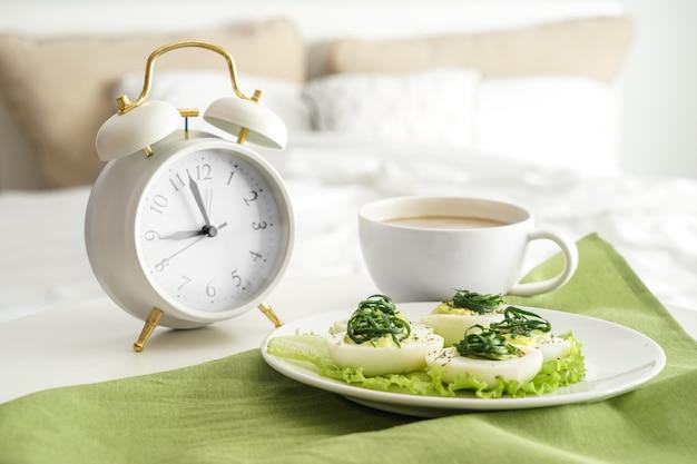 Assiette avec de savoureux œufs farcis et tasse de café sur le lit
