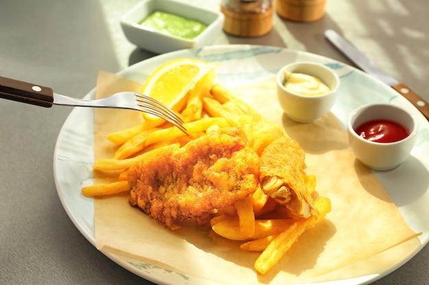 Assiette avec de savoureux poissons frits, frites et sauces sur table