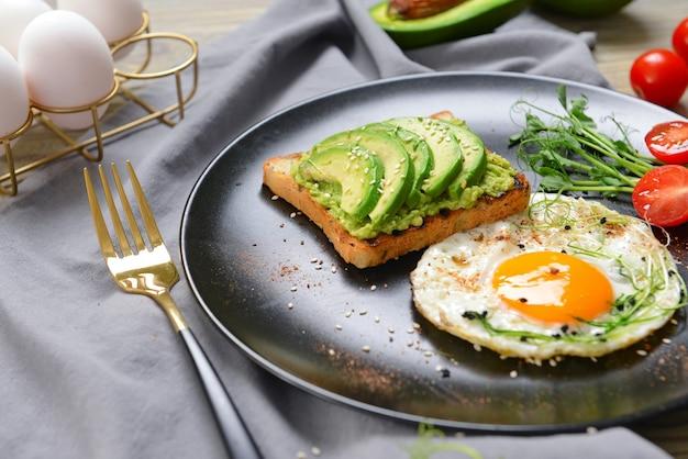 Assiette avec savoureux sandwich à l'avocat et œuf frit sur la table