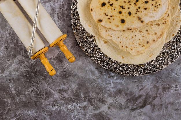 Assiette de seder de la pâque juive avec pain sans levain matsa et torah