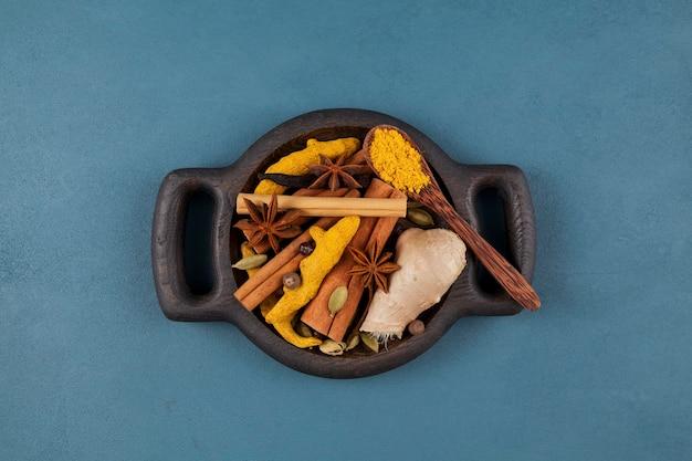 Assiette de service en bois avec ensemble d'épices épicées pour faire du thé indien masala (masala chai), lait doré et autres boissons.