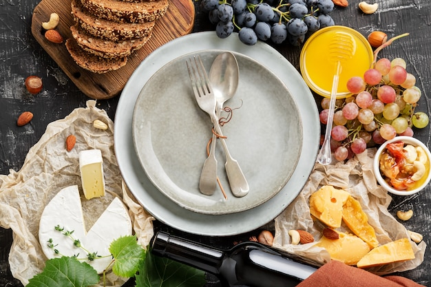 Assiette de service vide avec cuillère à fourchette dans le cadre d'ingrédients alimentaires gastronomie apéritif collations miel raisins fromage vin. maquette de l'espace de copie ou du modèle sur le dessus du plat de la plaque bleue longue bannière web.
