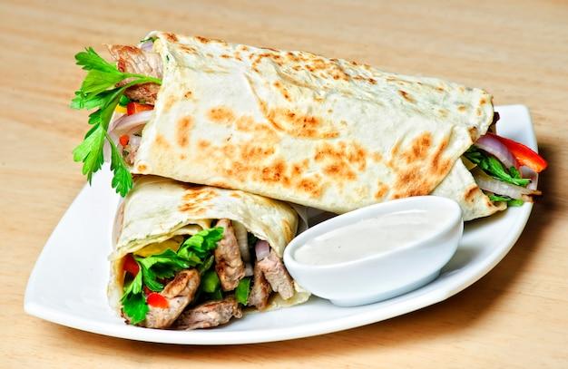 Assiette de shawarma traditionnelle orientale avec sauce.