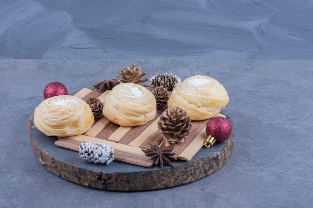 Une assiette sombre avec des biscuits et des pommes de pin de noël