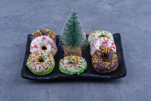 Une assiette sombre avec de délicieux beignets et un petit arbre de noël