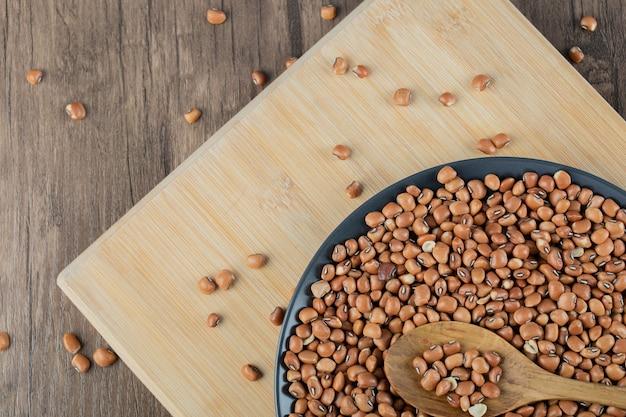 Une assiette sombre avec des haricots rouges crus sur une table en bois