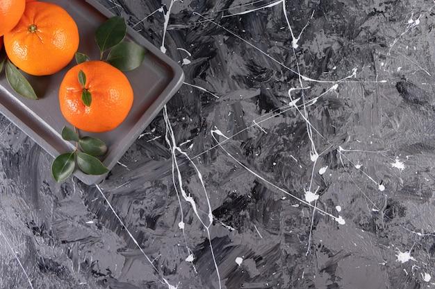 Assiette sombre d'oranges entières juteuses sur une surface en marbre
