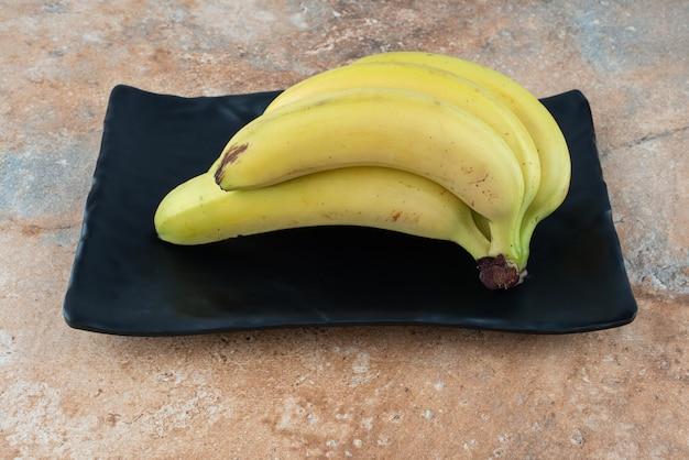 Une assiette sombre pleine de bananes fruits mûrs sur table grise.