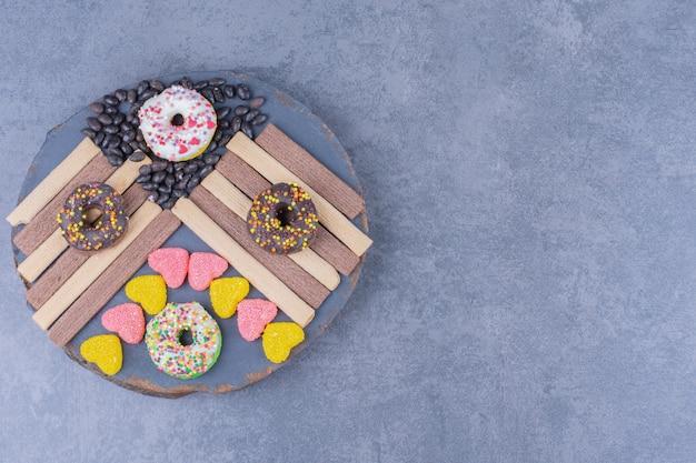 Une assiette sombre pleine de beignets et de bonbons à la gelée en forme de coeur