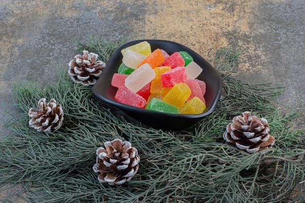 Une assiette sombre pleine de bonbons à la gelée de fruits sucrés et de pommes de pin. photo de haute qualité