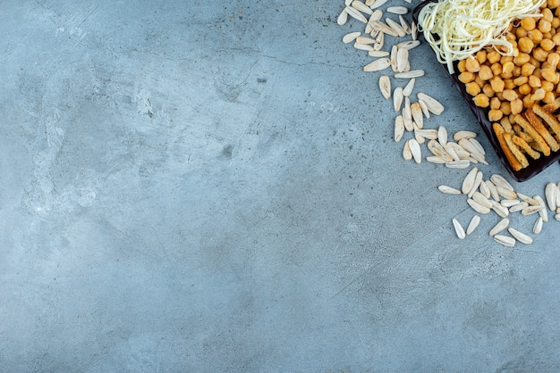 Une assiette sombre pleine de fromage et de petits pois sur fond gris. photo de haute qualité