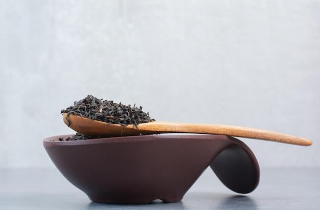 Une assiette sombre pleine d'infusion avec une cuillère en bois