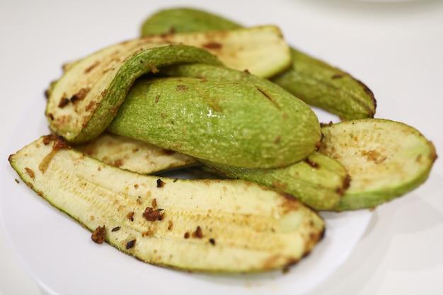 Sur une assiette sont cuites des courgettes avec assaisonnement et ail. le végétarisme et l'alimentation comme concept de mode de vie