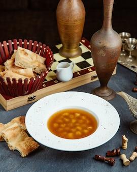 Assiette de soupe aux boulettes de dushbara servie avec du vinaigre et du pain